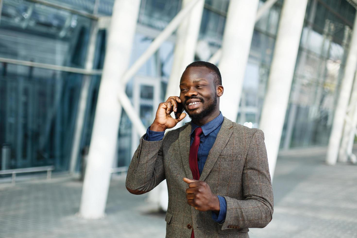 Elegante empresario afroamericano negro habla en su teléfono inteligente foto