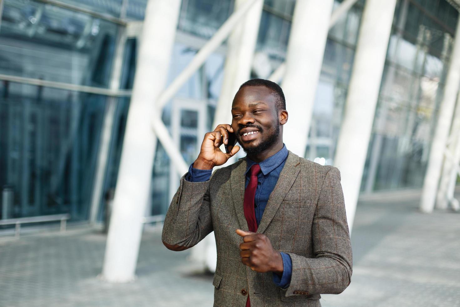 Stylish African American black businessman talks on his smartphone photo