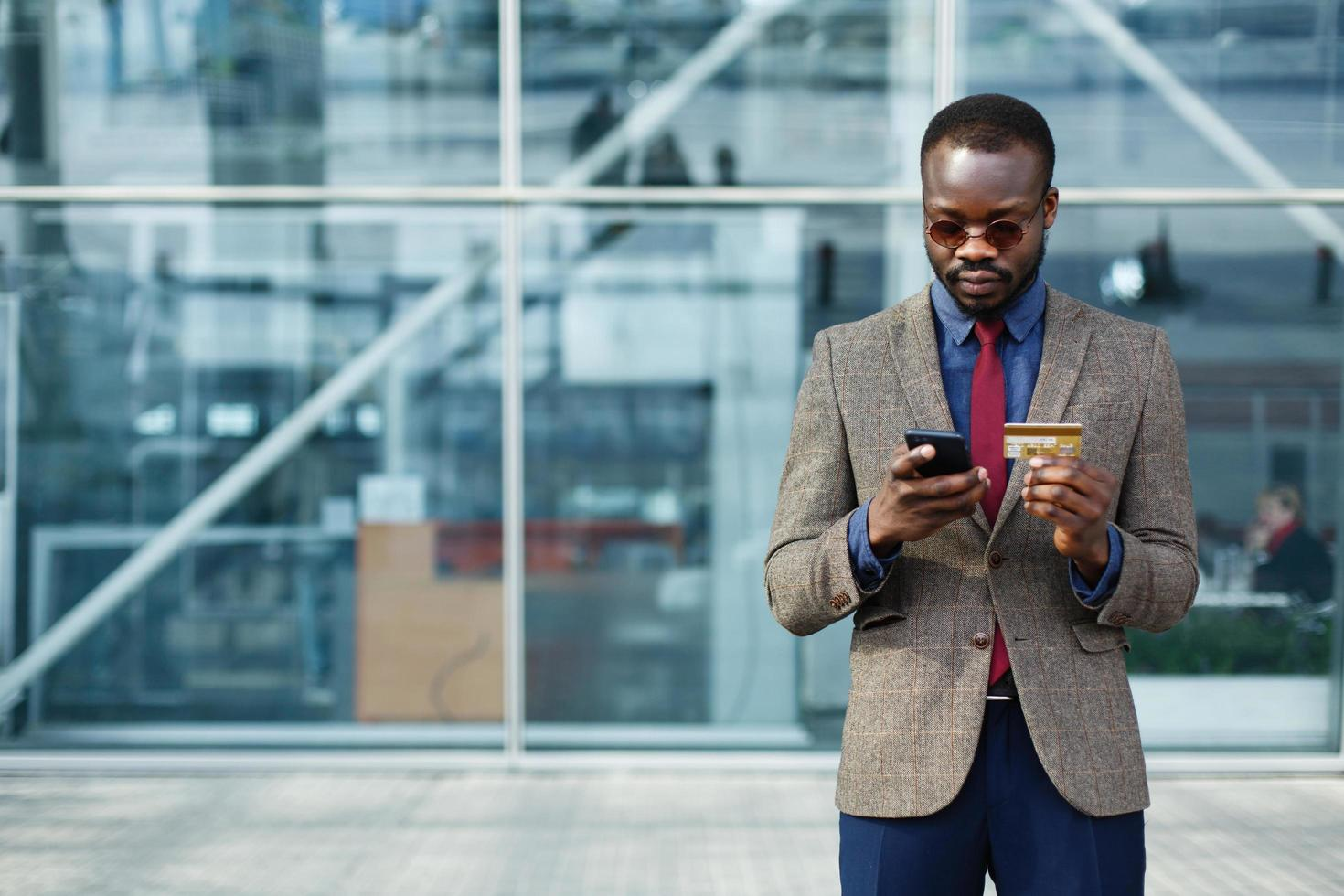 Stylish African American black businessman types information from his credit card photo