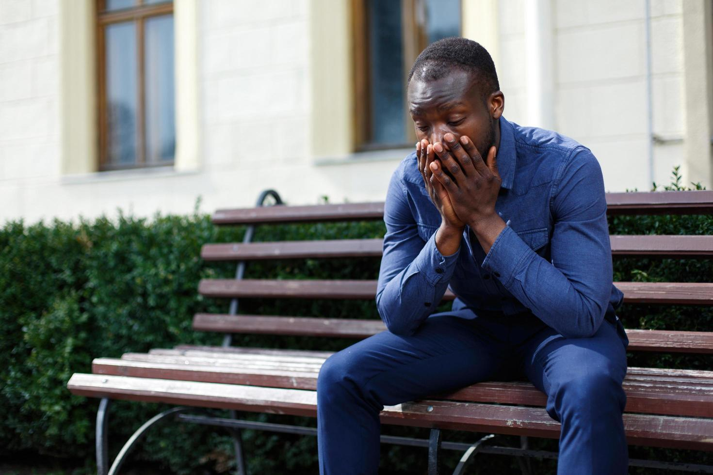 Tired African American man sits on the bench outside photo