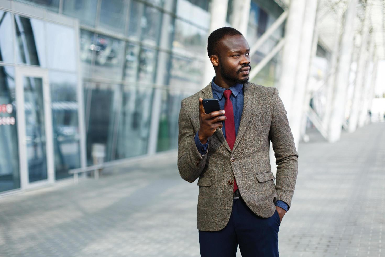 Stylish African American black businessman works on his smartphone photo