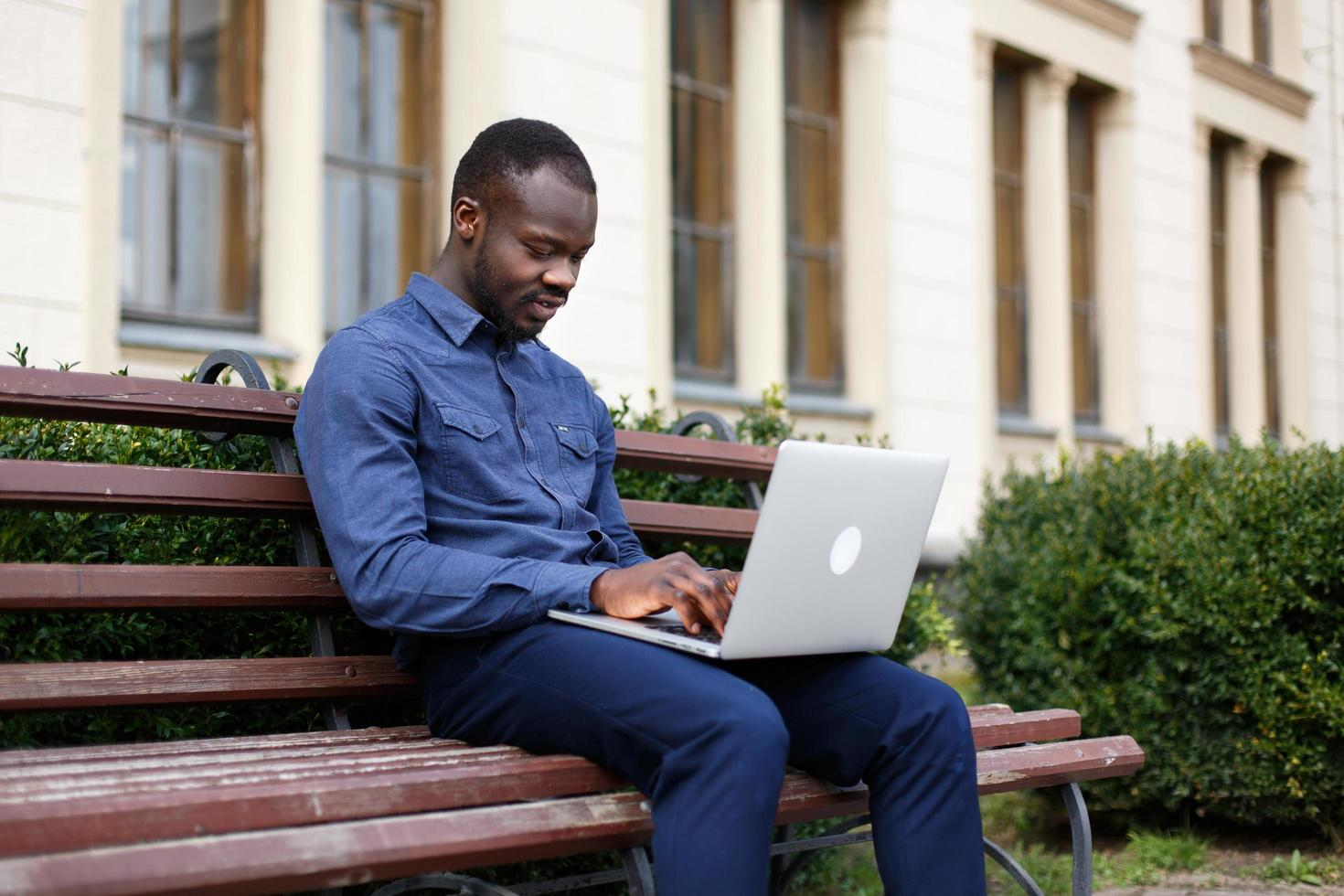 Happy African American man works on his laptop sitting on the bench outside photo