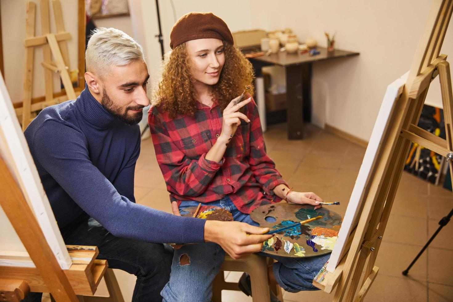 Stylish couple of artists draw a painting with oils photo