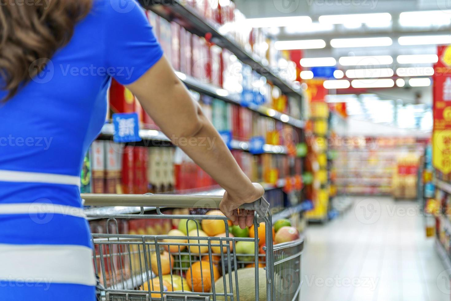 Señora empujando un carrito de compras en el supermercado. foto