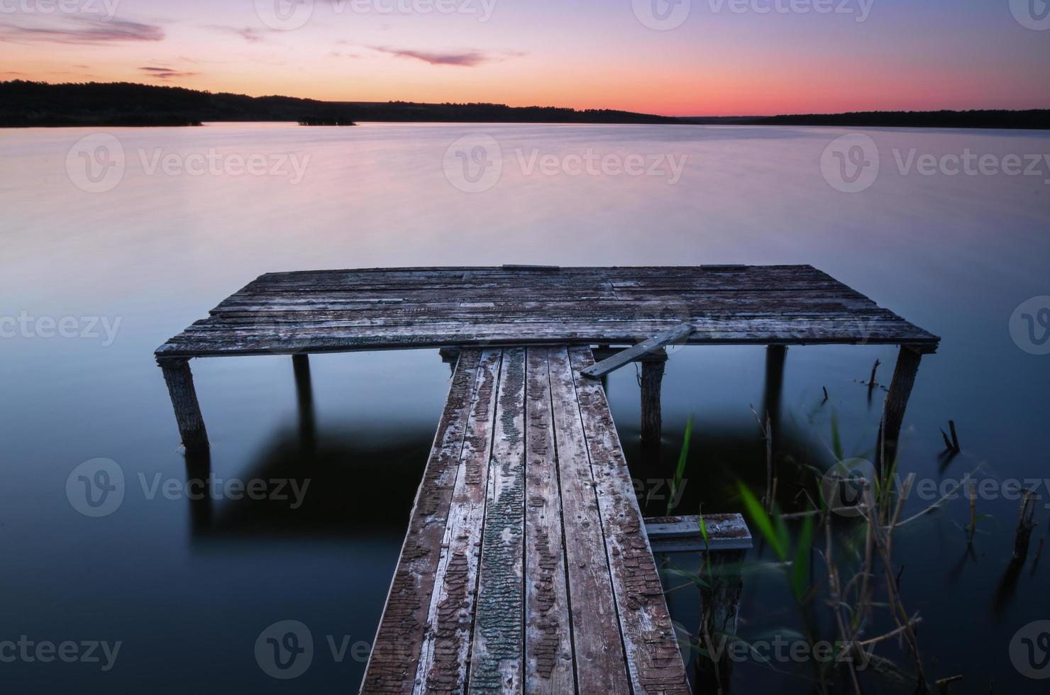Small wooden pier on big lake at sunset photo