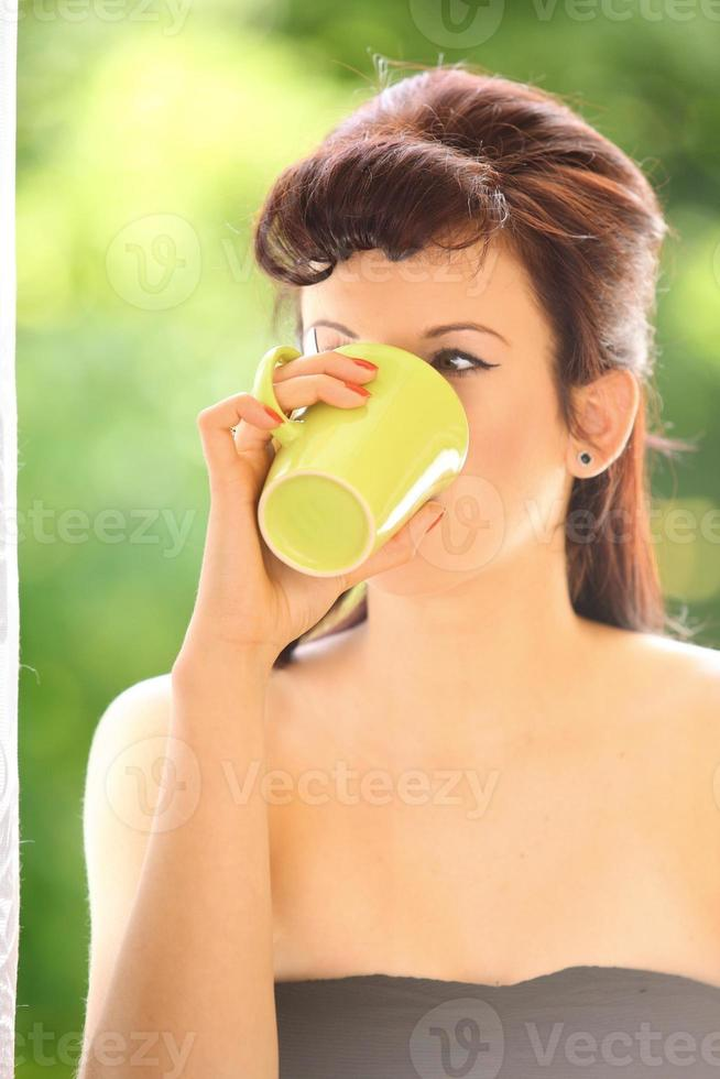 Beautiful Girl Drinking Tea or Coffee Indoor. Green Blurred Background photo