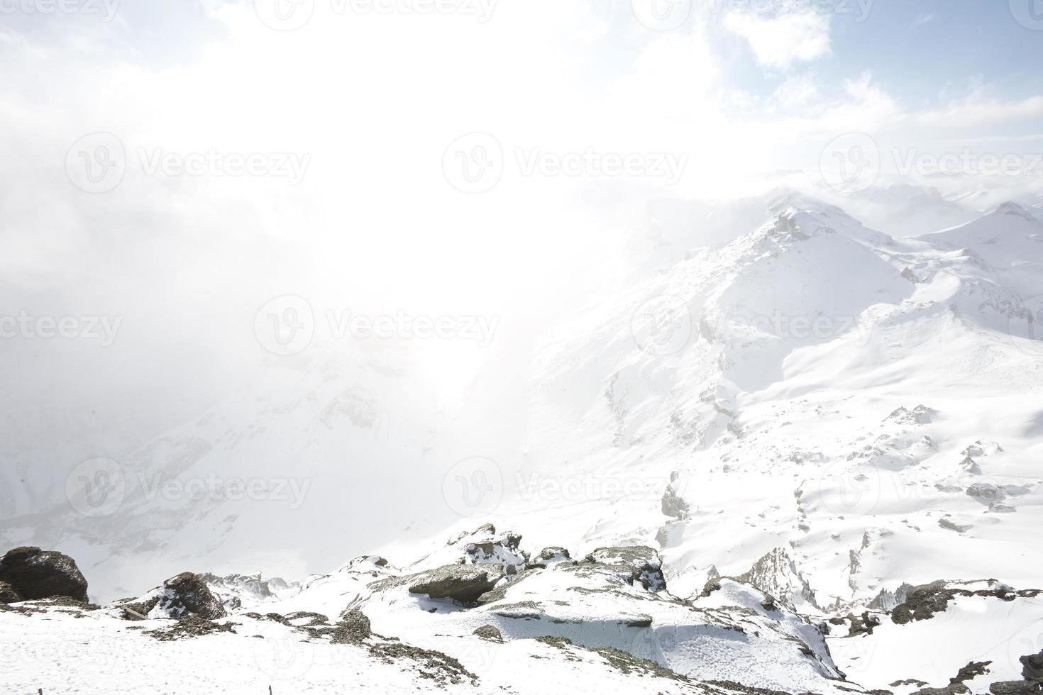 el polvo de nieve se acumula sobre el pico de la montaña foto