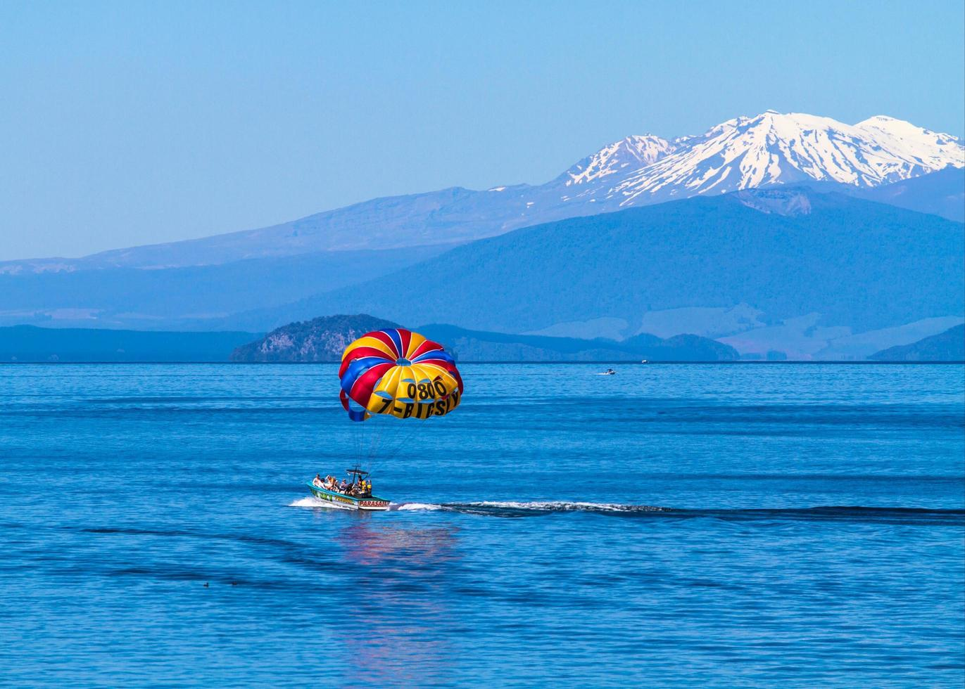 Lake Taupo, New Zealand, 2020 - A parasailing group riding on a boat near mountains photo
