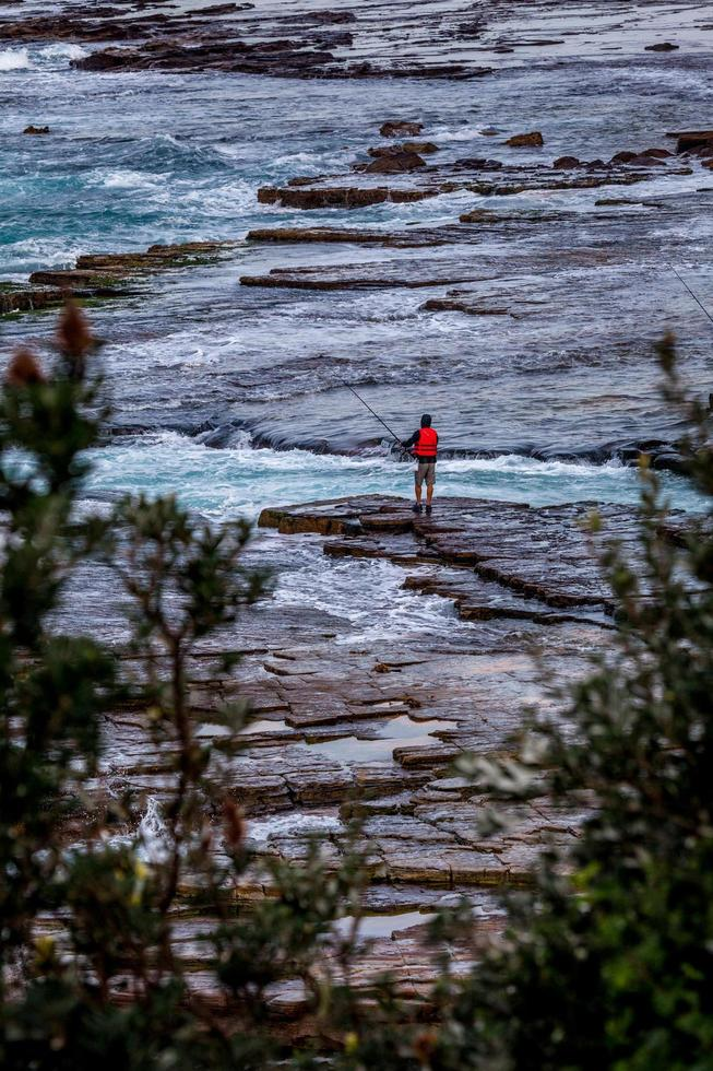 Sydney, Australia, 2020 - A view of a person on a rocky shore photo