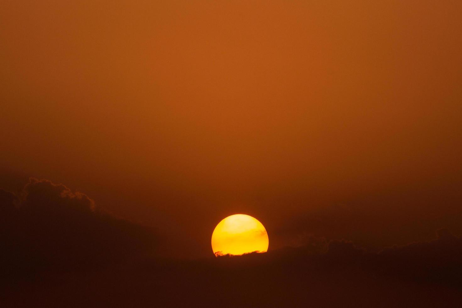 sol poniente detrás de las nubes foto