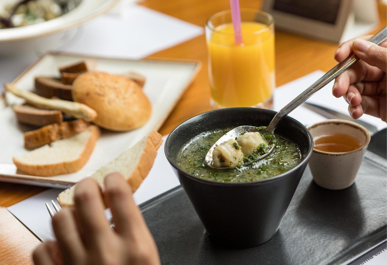 mujer comiendo sopa verde con salsa foto