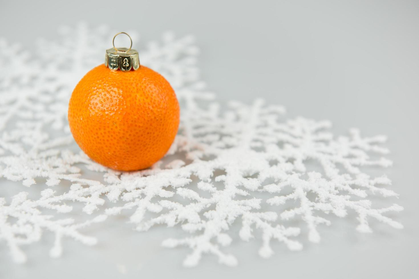 A tangerine bauble on a snowflake photo