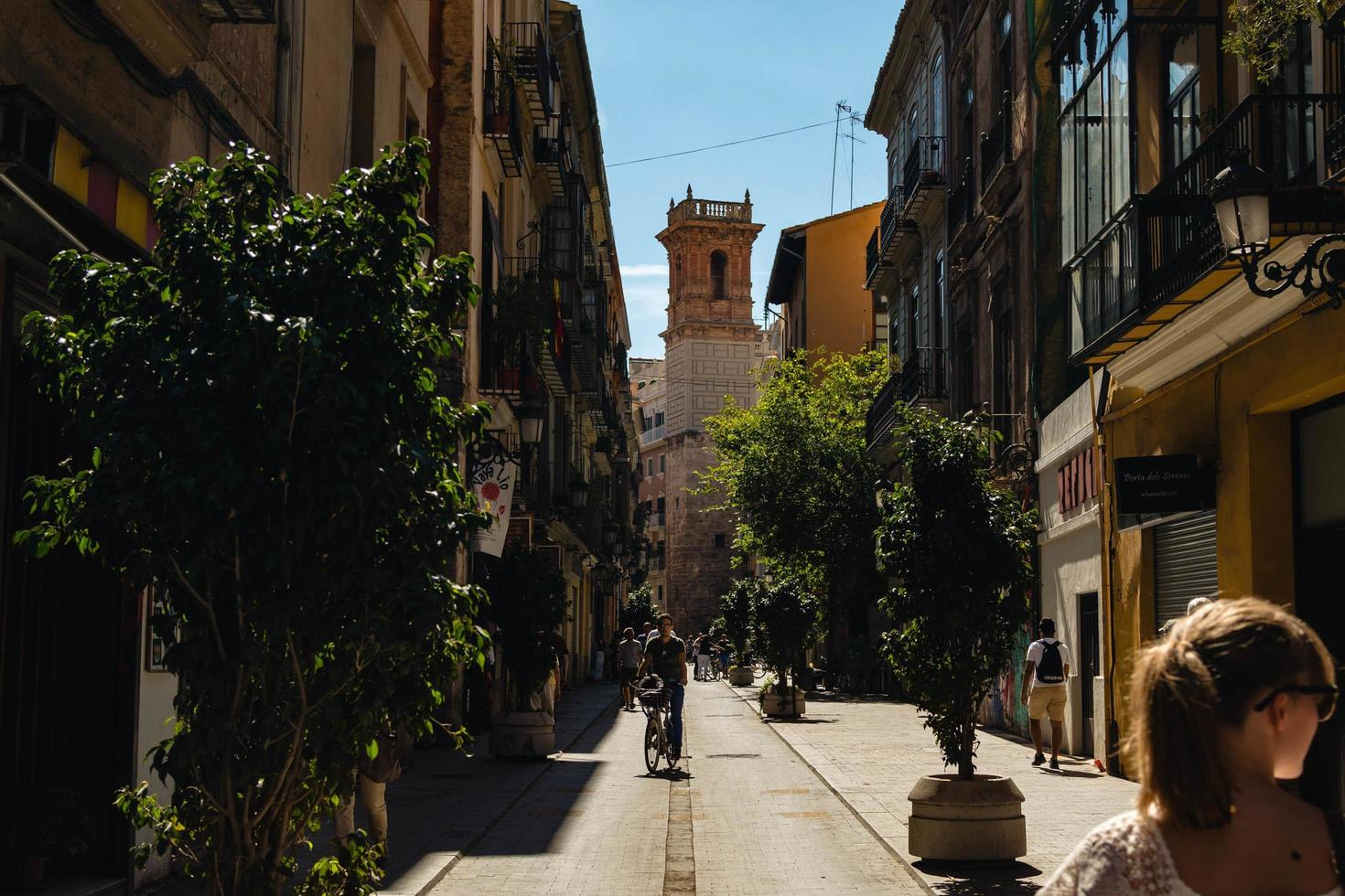 Valencia, Spain, 2017-Man riding bicycle in busy alley photo