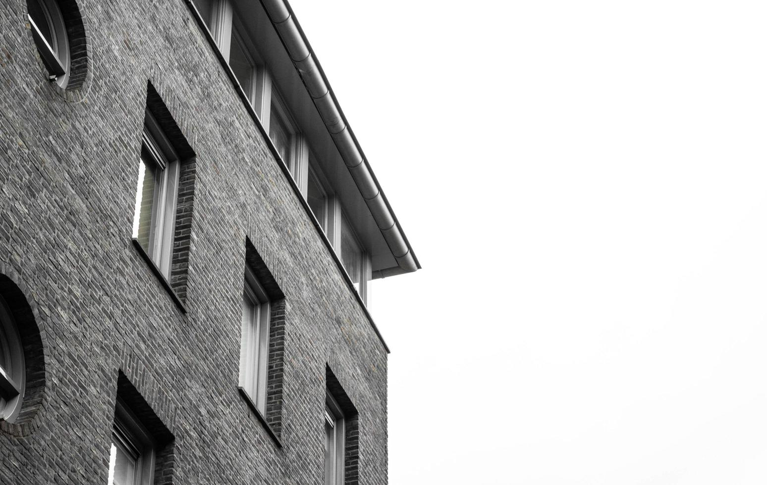 Grayscale of a brick building photo