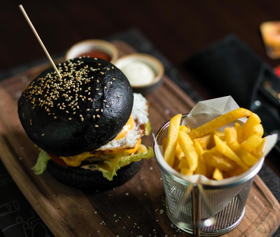 Black bread burger with French fried potatoes photo