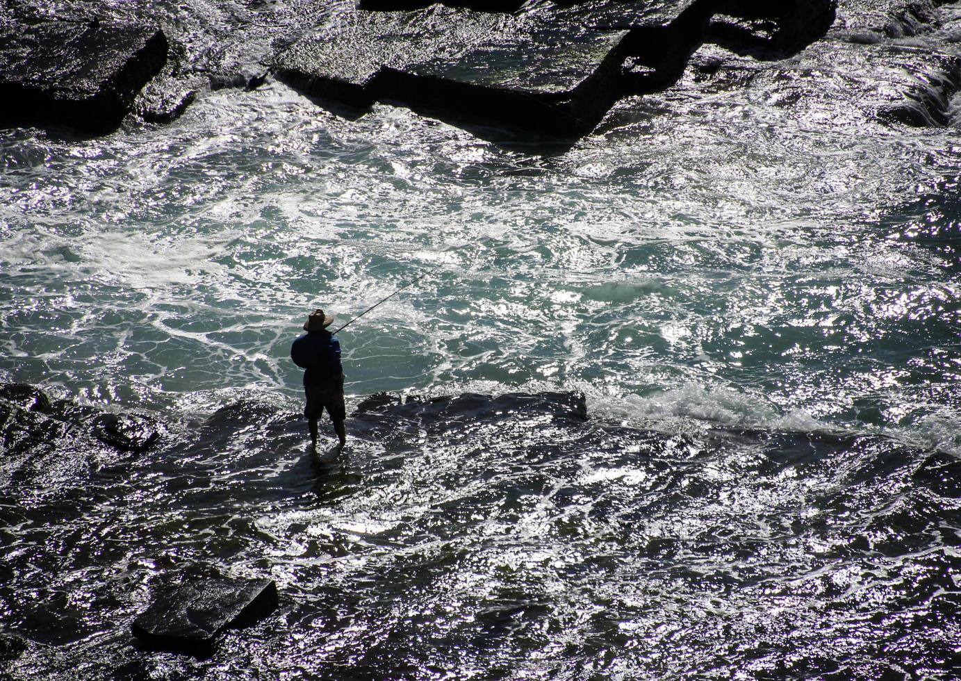 Sydney, Australia, 2020 - Man fishing while wading in the water photo