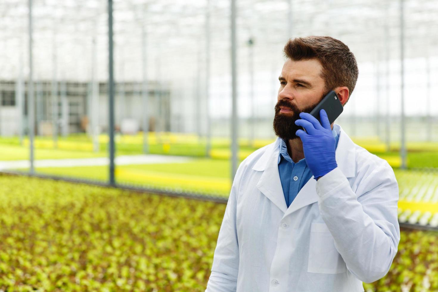 hombre en bata de laboratorio hablando por teléfono foto