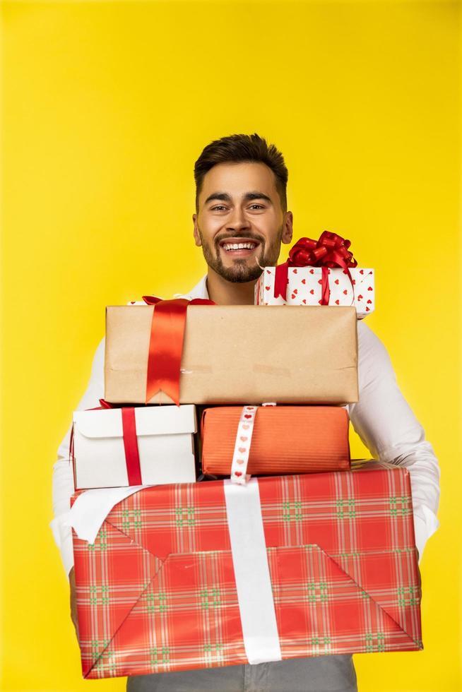 chico guapo sonriente sosteniendo cajas de regalo foto