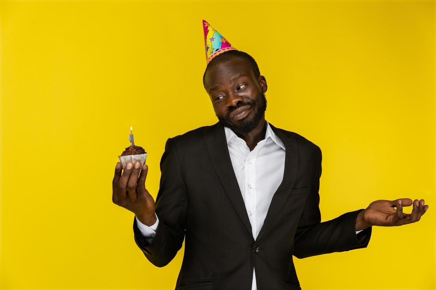 apuesto hombre de negocios parece perdido mientras sostiene un pastel de cumpleaños foto