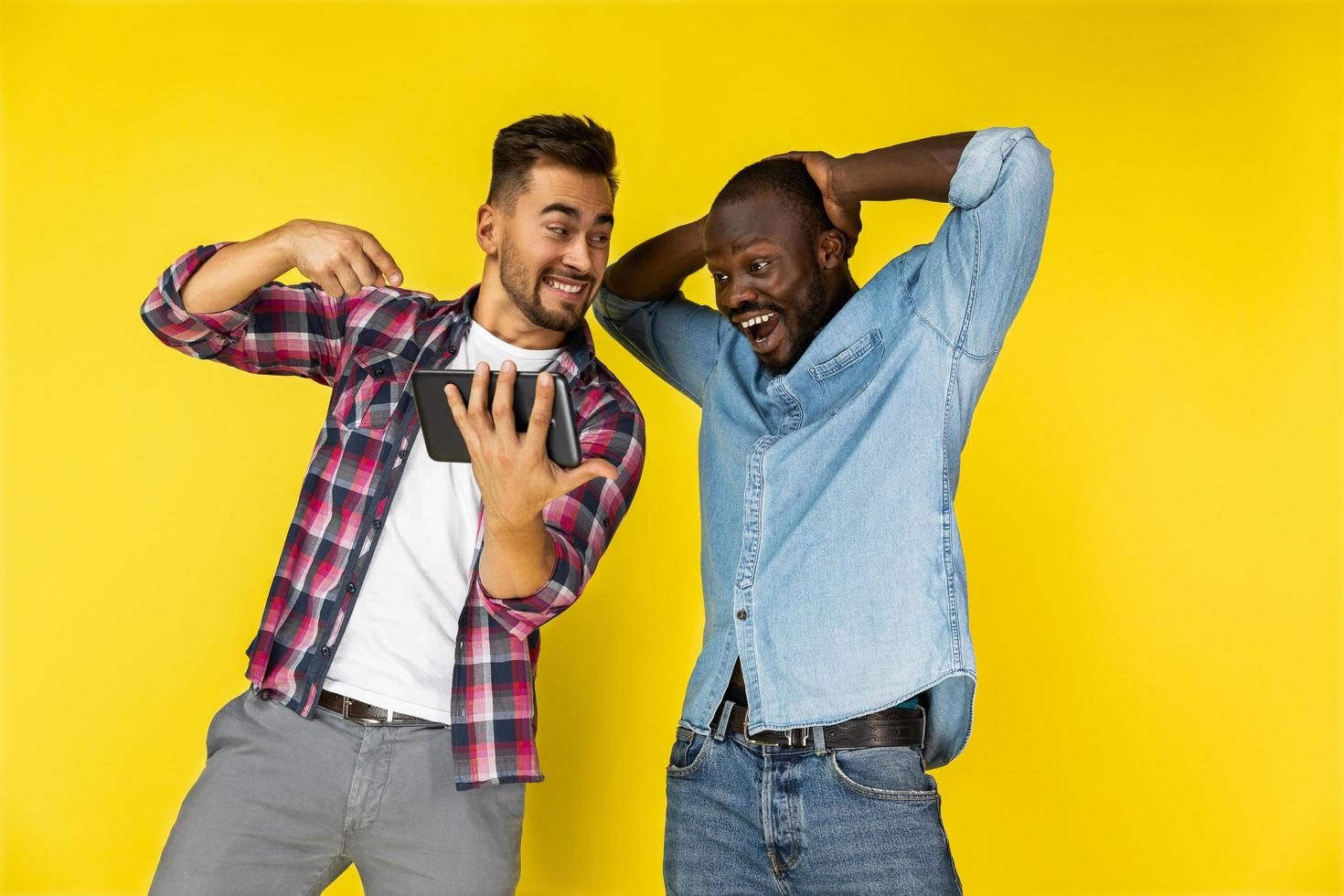 European and black man delighted of watching the tablet photo