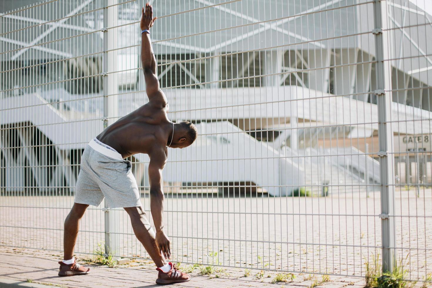 Man stretching near a fence photo
