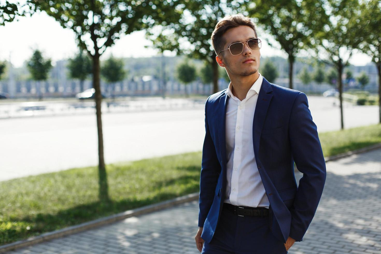 Handsome man in a business suit walks along the street photo