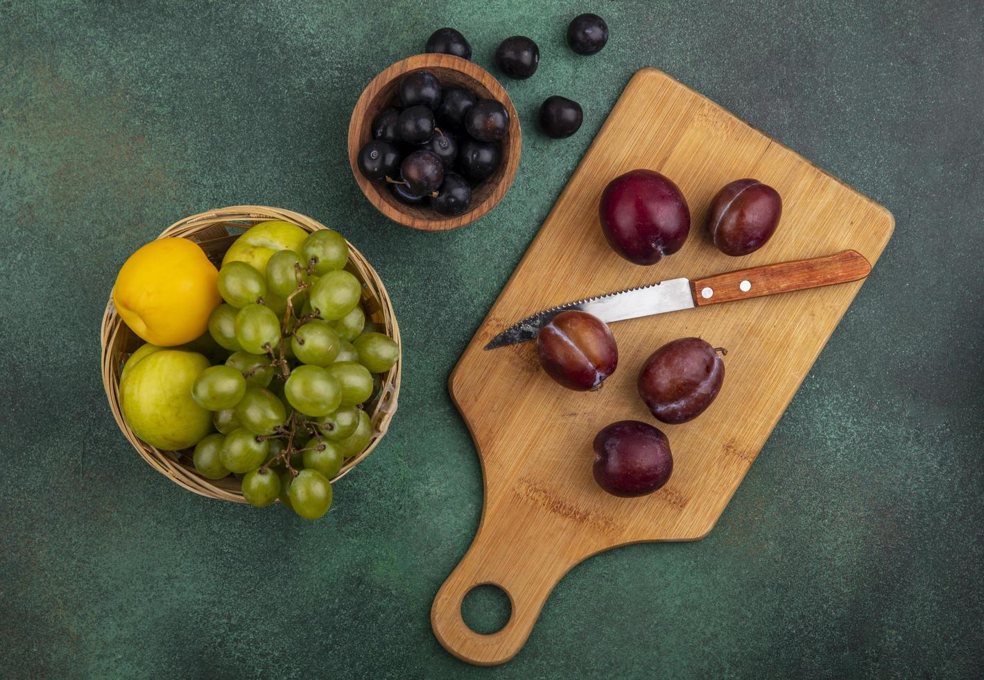 Surtido de frutas en la tabla de cortar sobre fondo verde foto