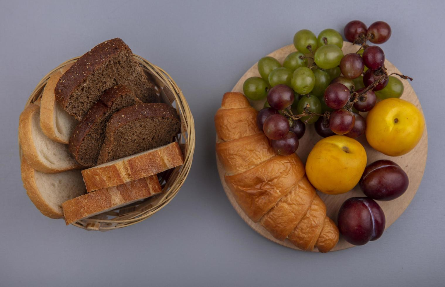 Assorted fruit and bread on neutral background photo