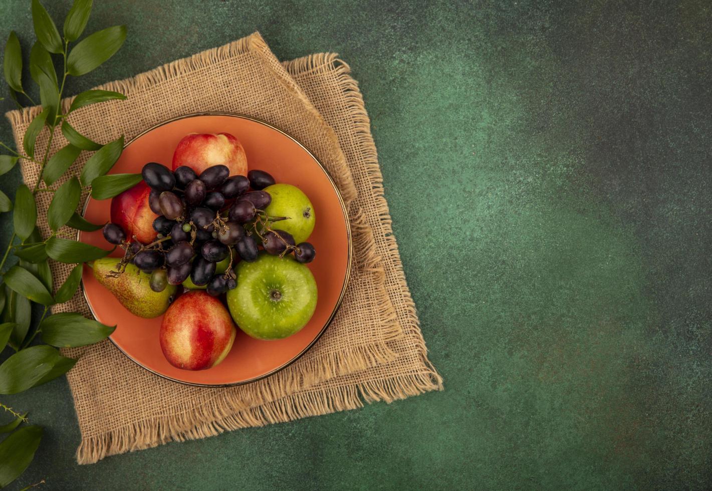 Fruta variada sobre fondo verde estilizado foto