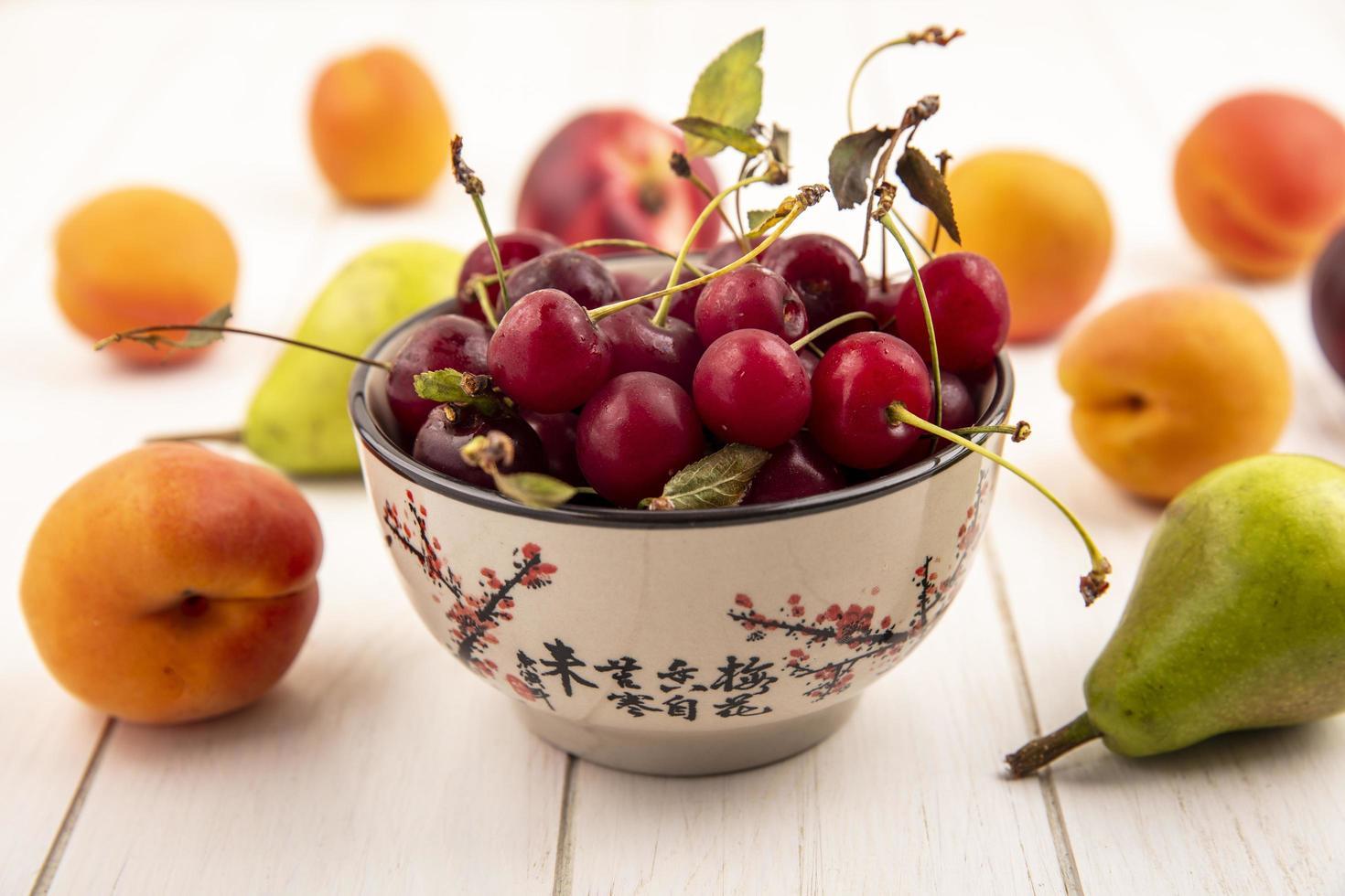 Tazón de cerezas con frutas sobre fondo de madera foto