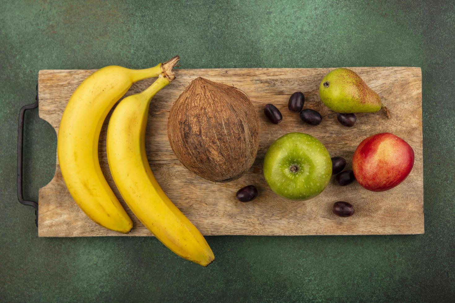 Assorted fruit on cutting board on green background photo