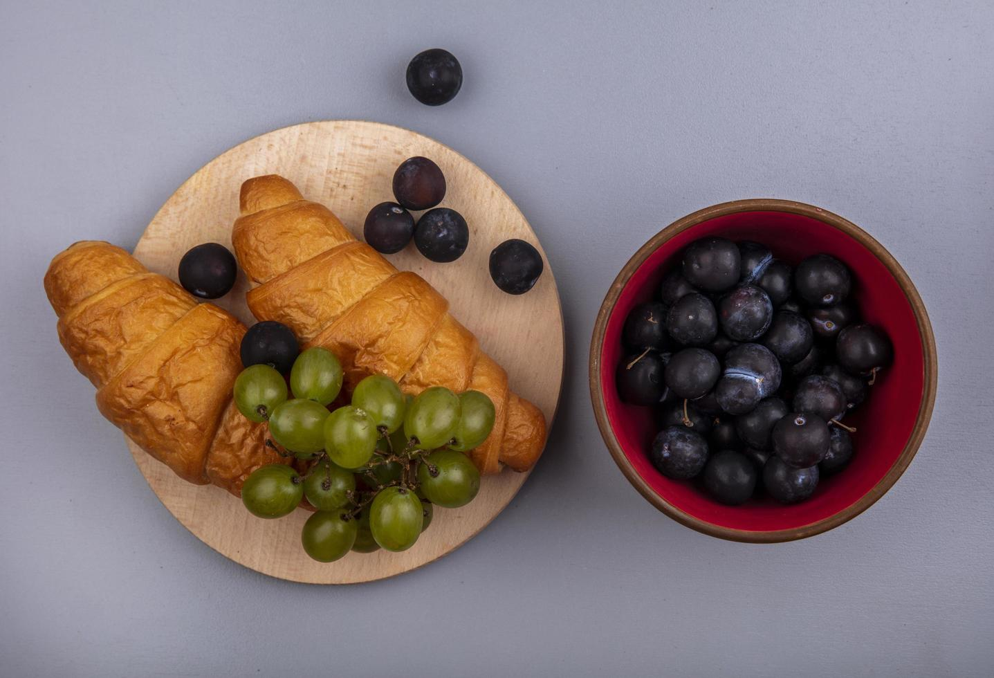 Top view of fruit with croissants on gray background photo