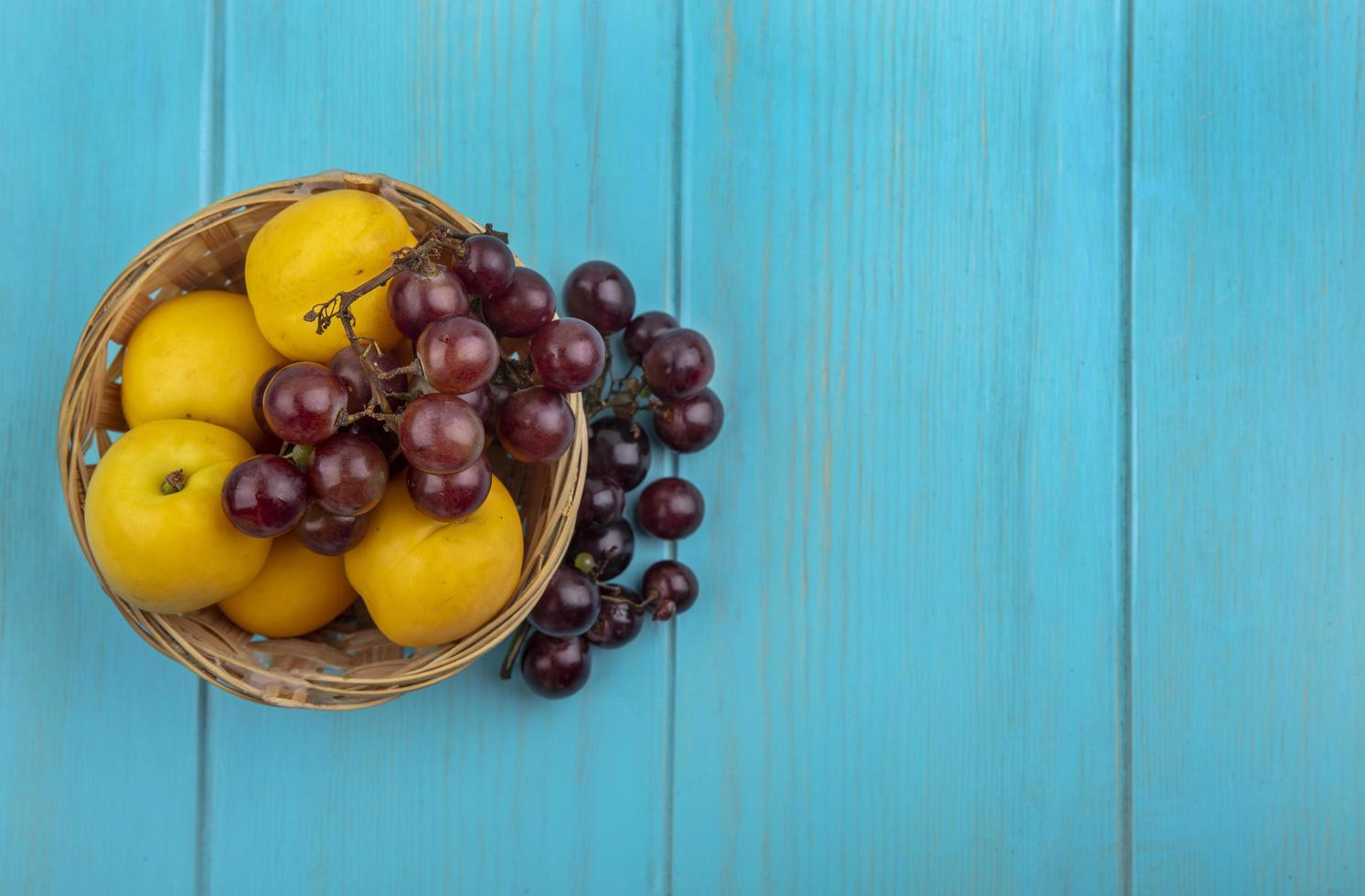 Assorted fruit in a basket on blue background photo