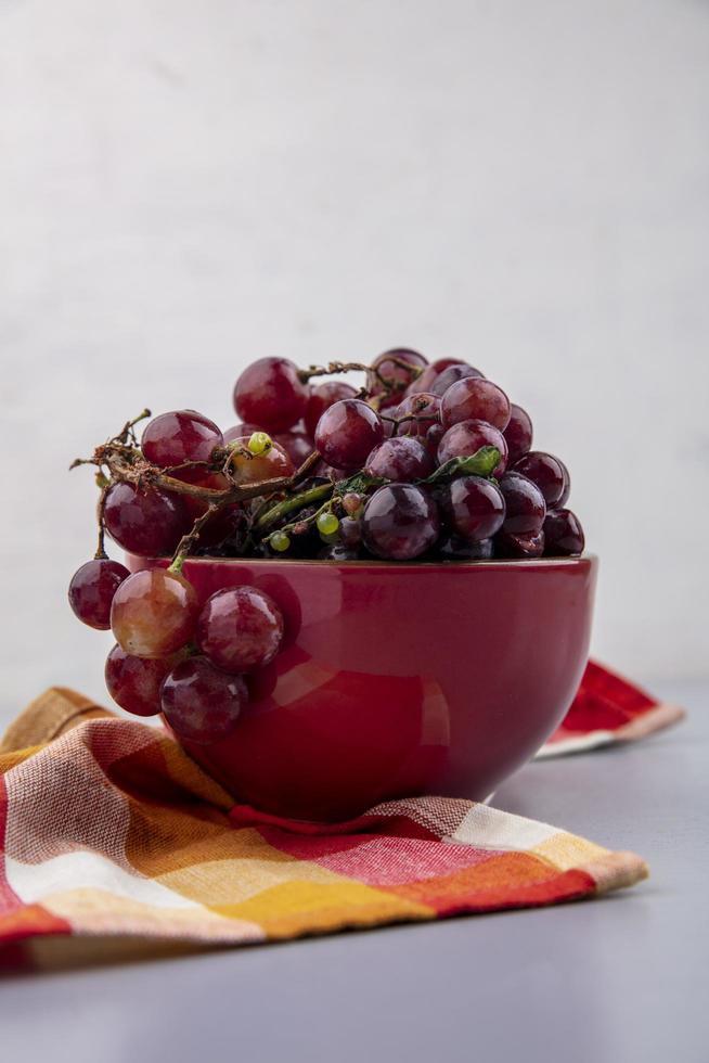 Uvas rojas en un recipiente sobre tela escocesa y fondo gris foto