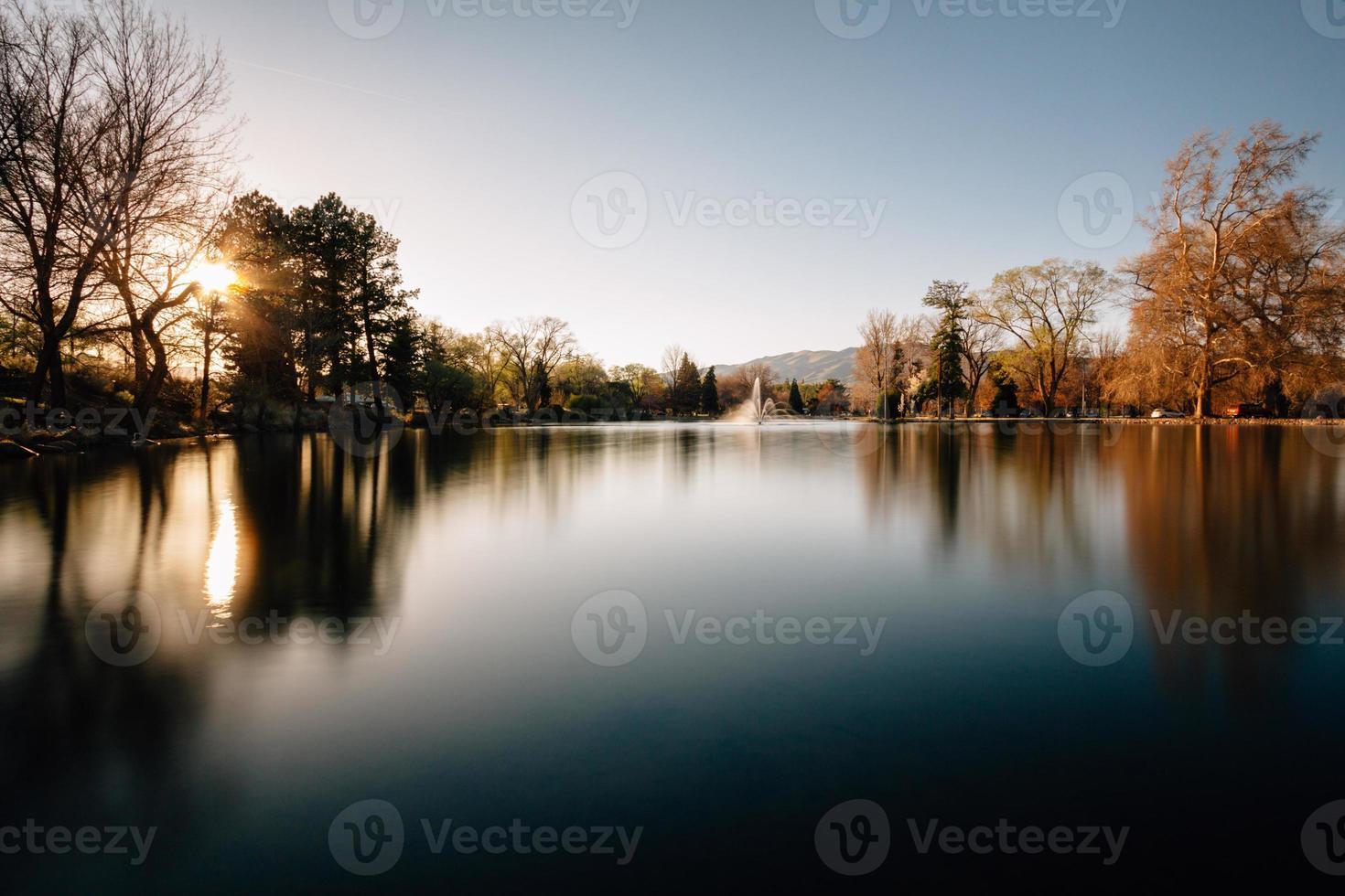 puesta de sol sobre un estanque del parque foto