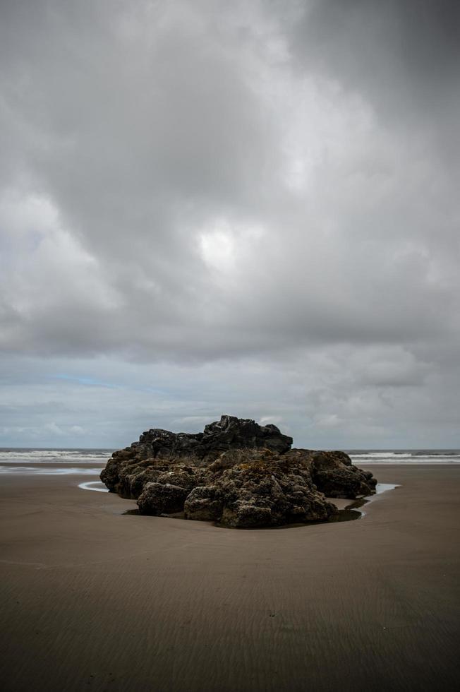 Formación de roca marrón en una playa foto