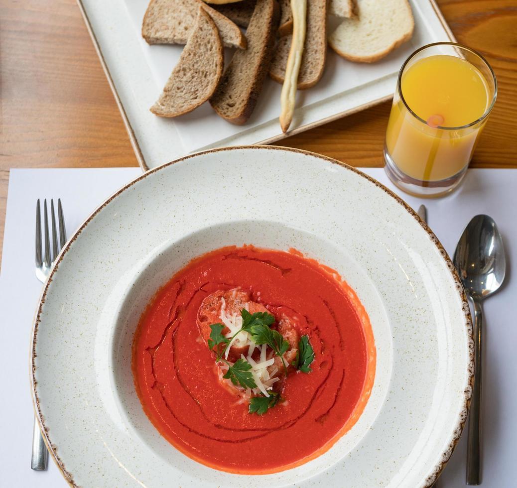 sopa de tomate con jugo de naranja y pan foto