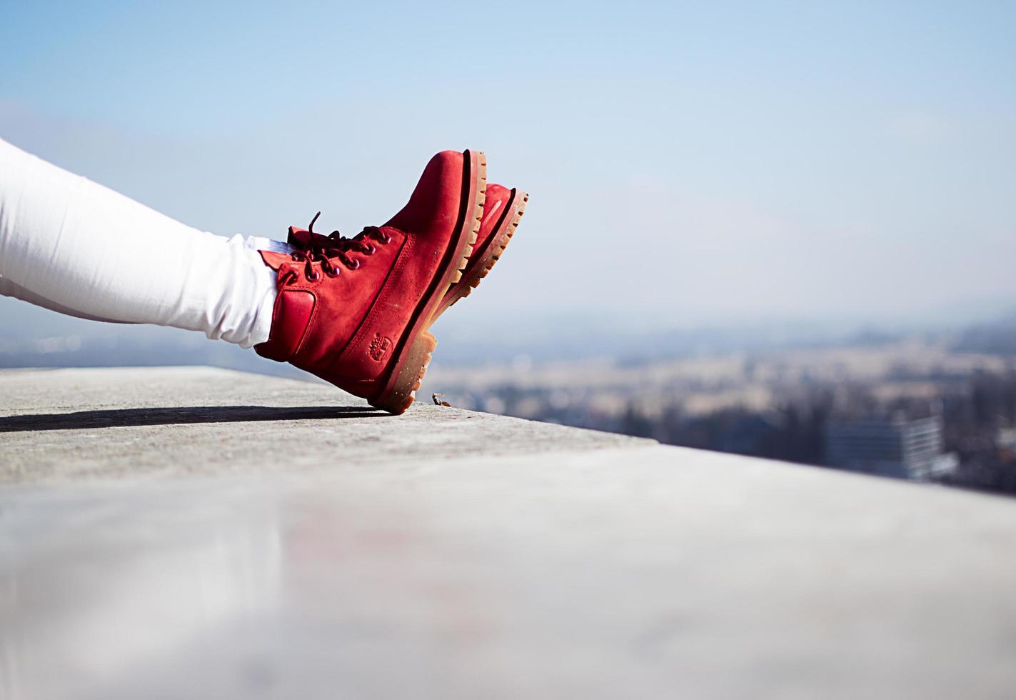 Eslovenia, 2020 - persona con botas rojas en una azotea en una ciudad foto