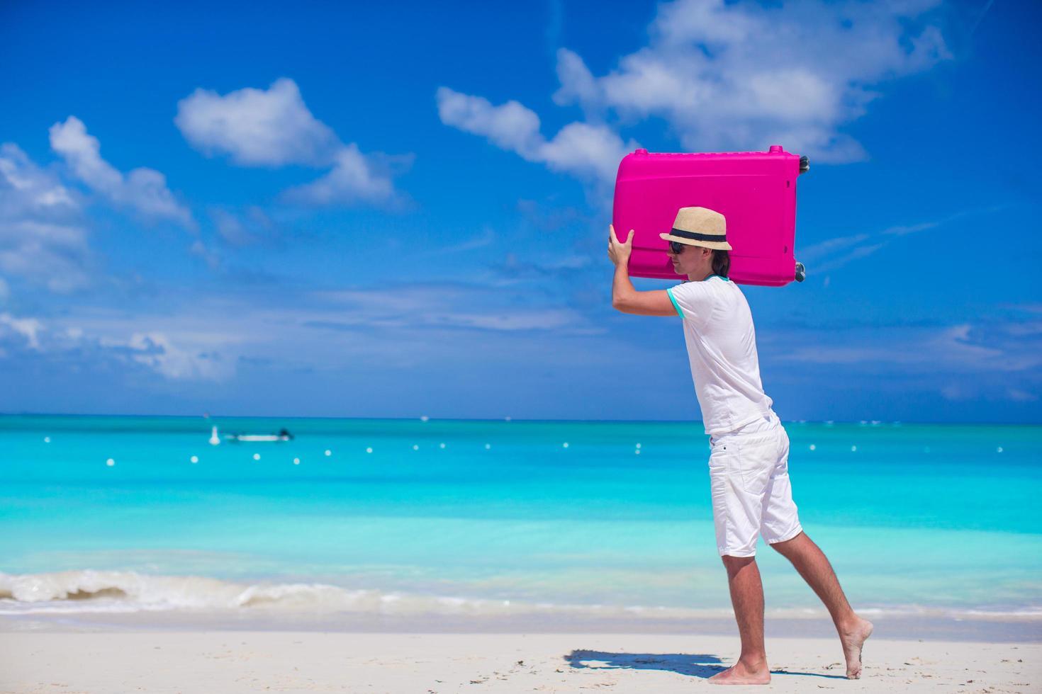 Hombre acarreando una maleta en la playa foto