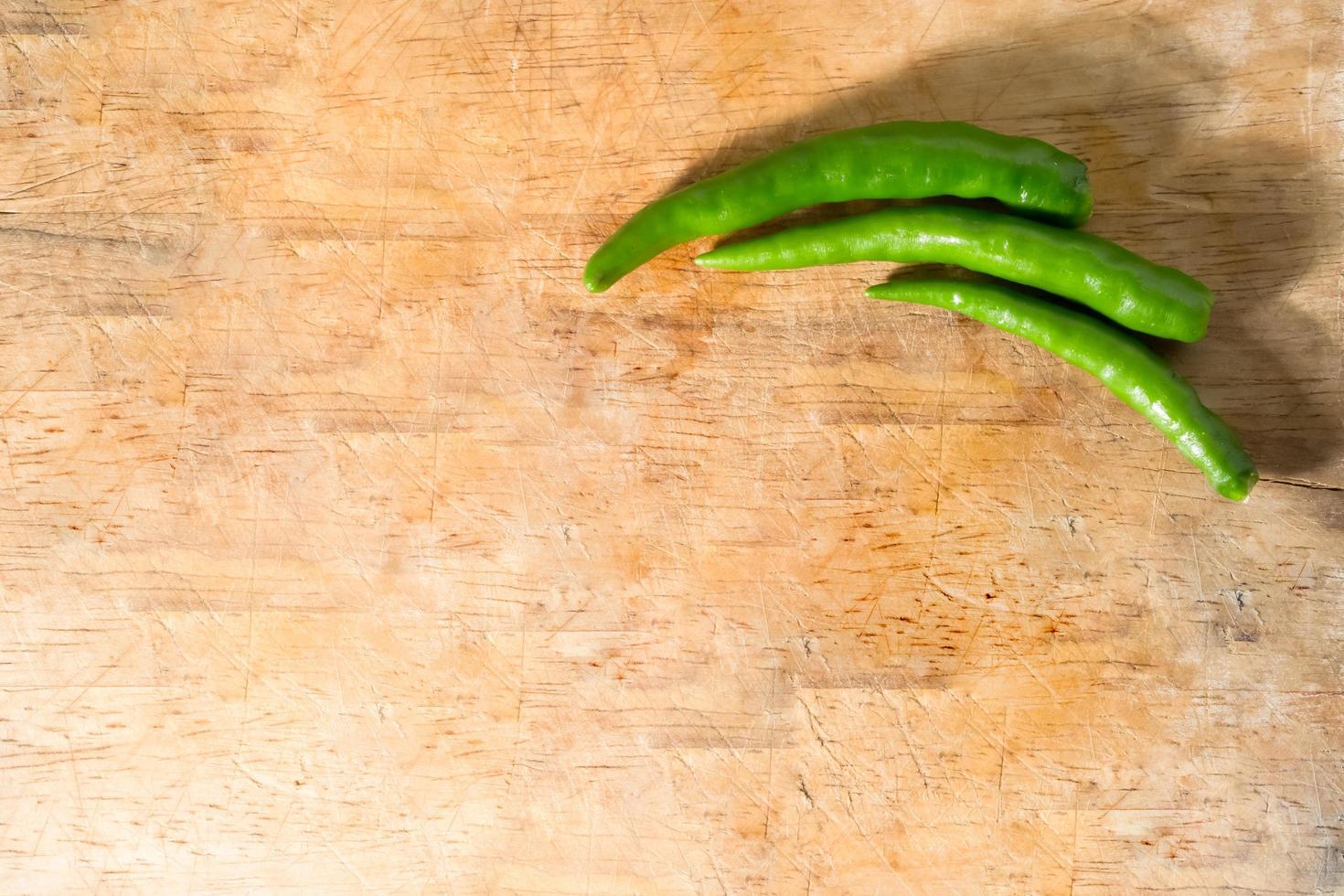 chiles verdes sobre fondo de madera foto