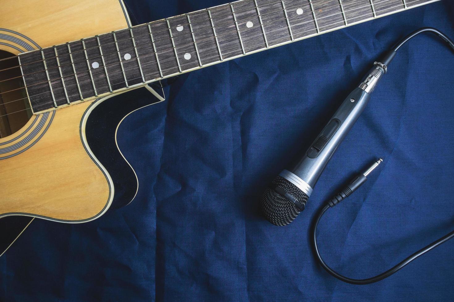 micrófono y guitarra acústica en la mesa foto