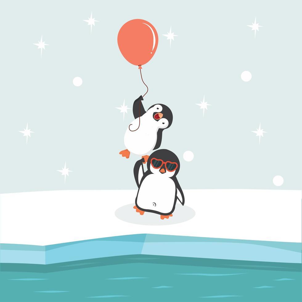 pingüinos sosteniendo globo vector