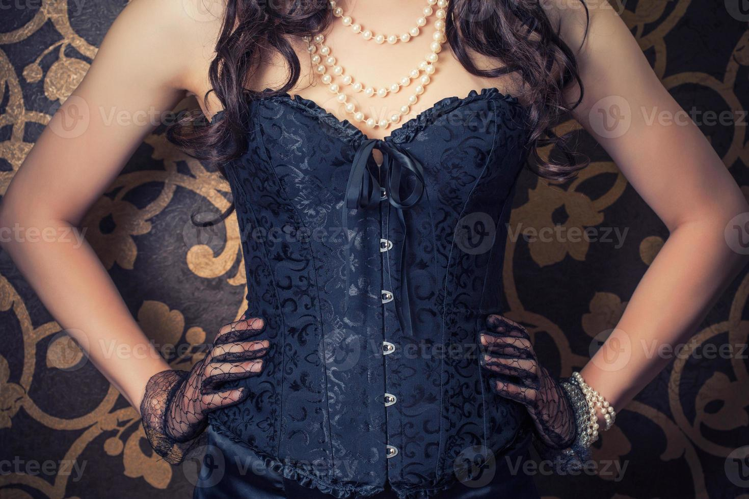 woman wearing black corset and pearls against retro background photo