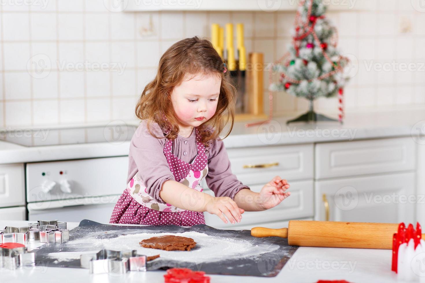 Niña hornear galletas de jengibre en la cocina doméstica foto