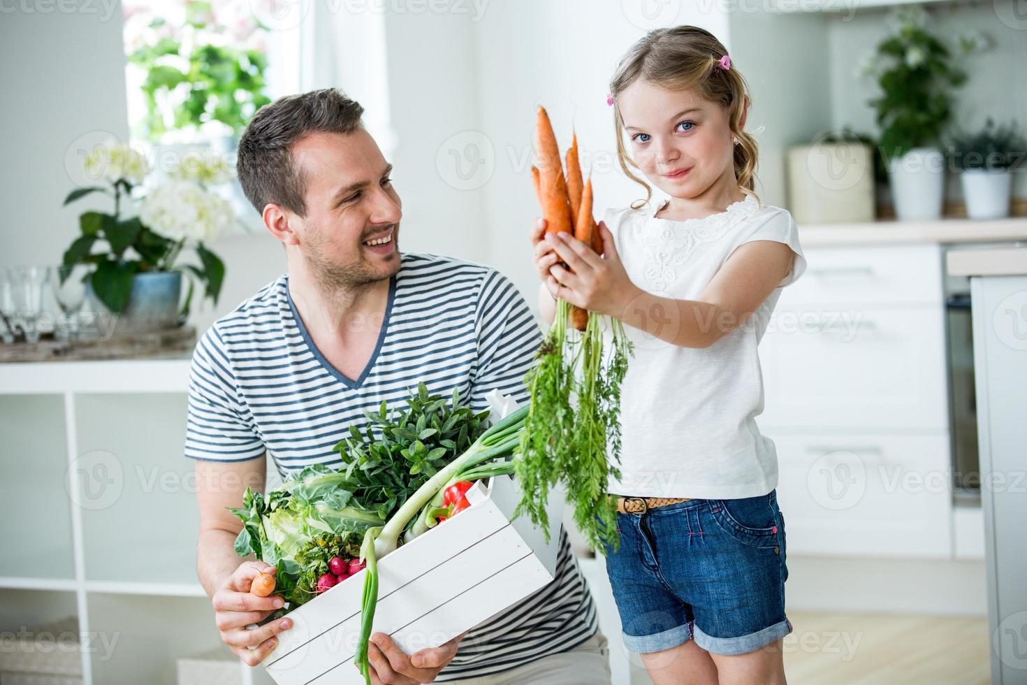 Father and daughter with vegetable box in kitchen photo