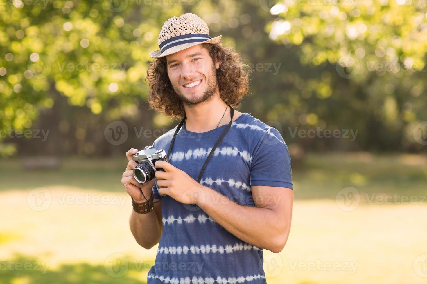 Handsome hipster using vintage camera photo