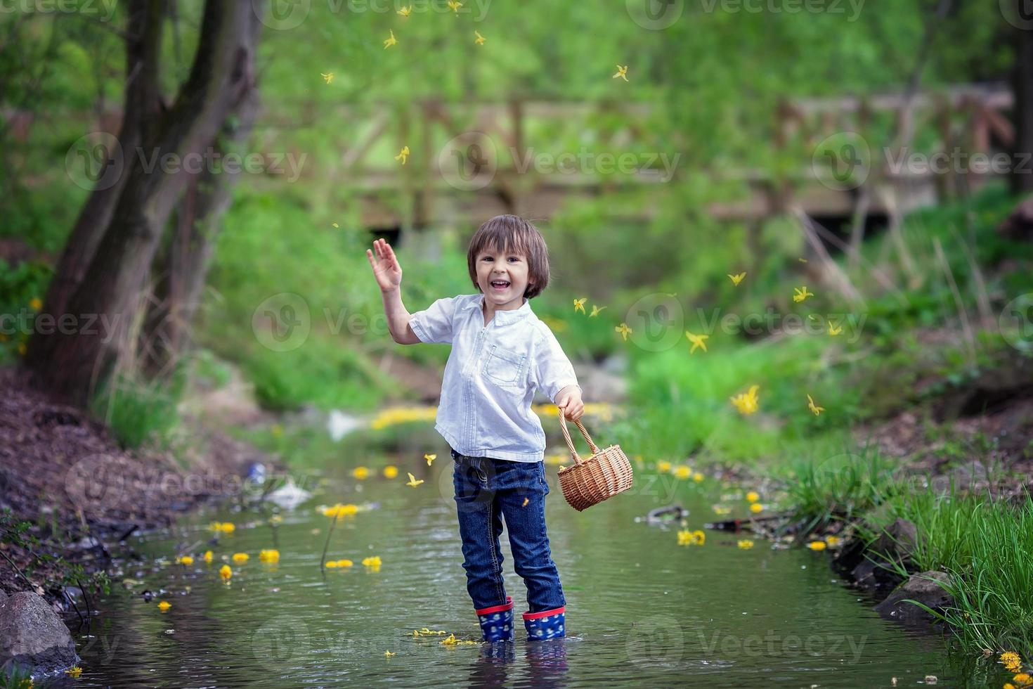 Adorable boy with little basket, full of flowers photo