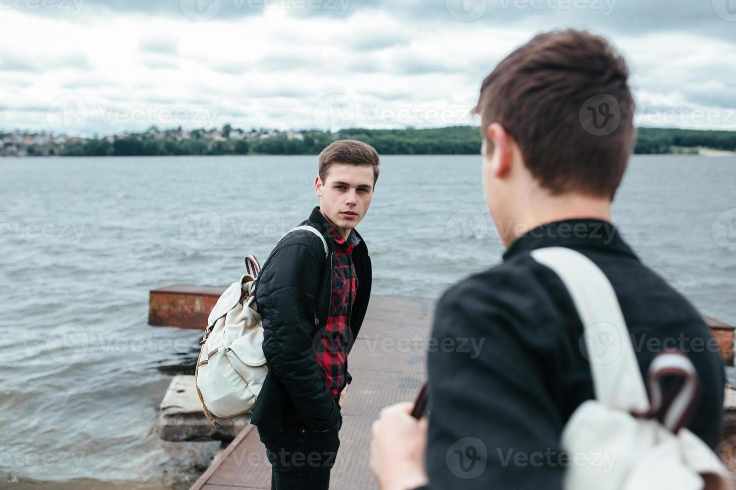 two young guys standing on a pier photo