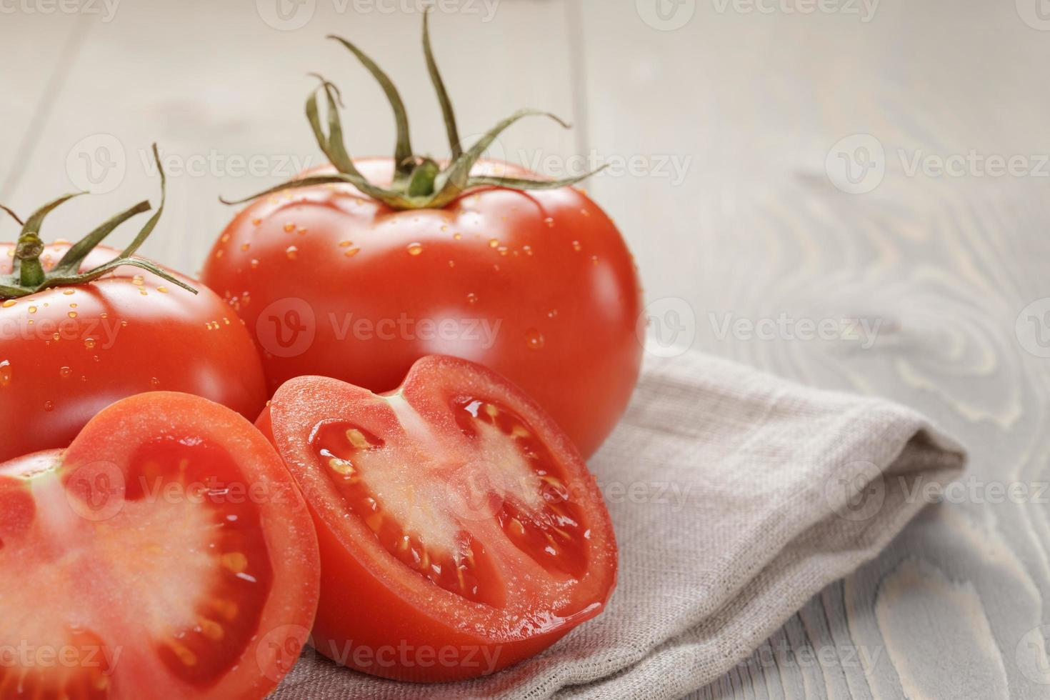 fresh ripe tomatoes with halfs on wood table photo