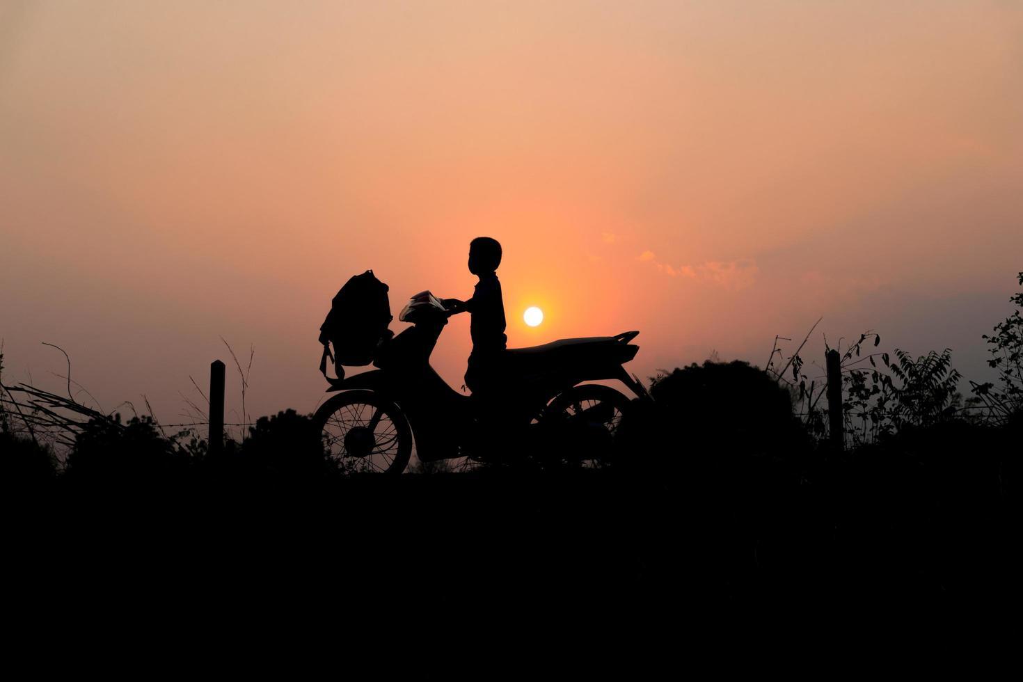 silueta de niño en una motocicleta foto
